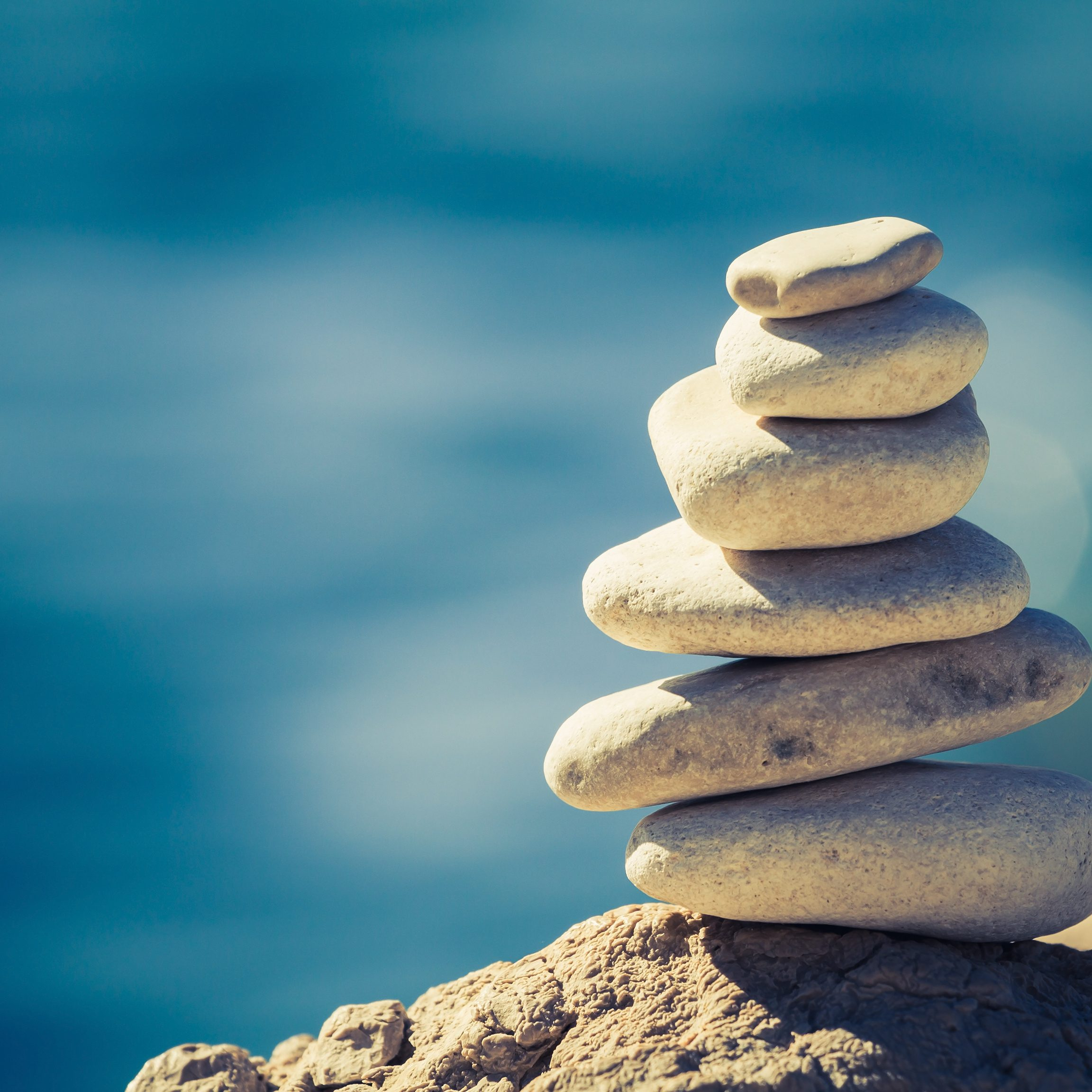 Balance and wellness retro spa concept, inspiration, zen-like and well being tranquil composition. Close-up of white pebbles stack over blue sea